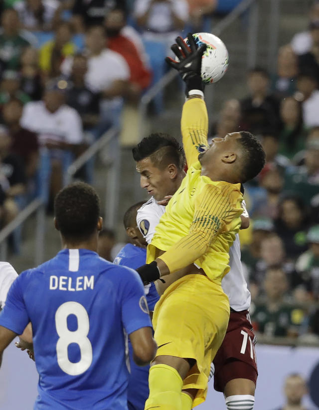 Martinique's goalkeeper Loic Chauvet, right, blocks a shot by Mexico's Roberto Alvarado (11) during the first half of a CONCACAF Golf Cup soccer match in Charlotte, N.C., Sunday, June 23, 2019. (AP Photo/Chuck Burton)