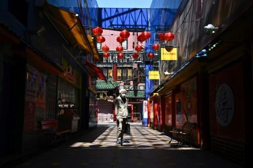 A man wearing a face mask stands in lane in the Chinatown area of Yokohama
