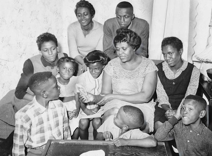 Helen Arnold holds the $350 she received from a Secret Santa in 1960. From left, her children are John, 12, Mona, 14, Donna, 5, Cathy, 19, Carla, 8, Royal, 16, Gerald, 7, Gale, 13, and Gary, 10. The children attended Bryan Elementary, Jennings Junior High and North High.