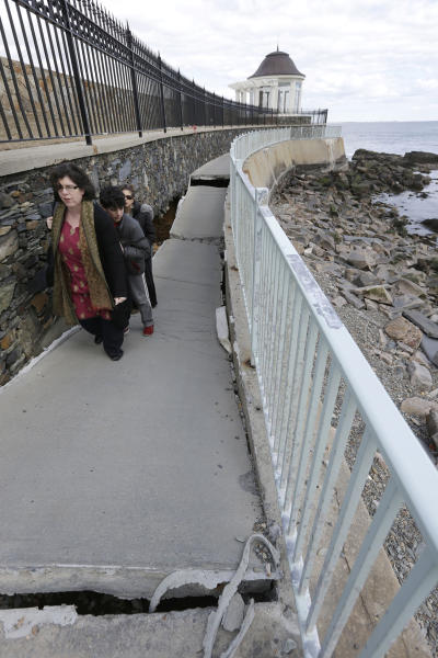 FILE - In this Wednesday, March 27, 2013 file photo, Jeanine Chada, of New York, front left, makes her way along a sunken and damaged portion of the Cliff Walk, in Newport, R.I. Large portions of the Cliff Walk damaged by Superstorm Sandy have yet to be repaired as the summer tourist season approaches. (AP Photo/Steven Senne, File)