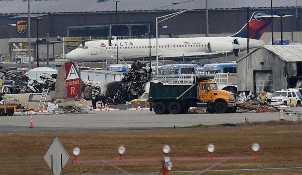 PHOTO: A Delta commercial airline plane taxis to take-off behind investigators at the wreckage of World War II-era bomber plane that crashed at Bradley International Airport in Windsor Locks, Conn., Oct. 2, 2019. (Jessica Hill/AP)