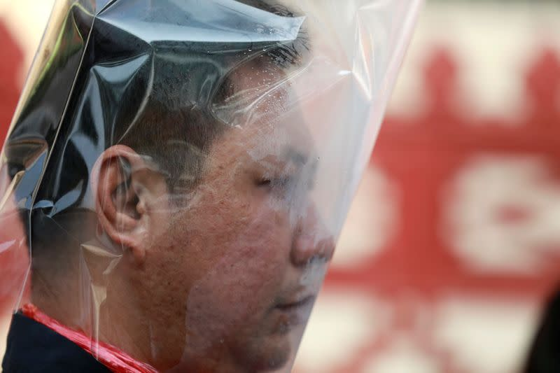 A man wears a plastic bag on his head during an environmental activists' rally to demand rights to clean air, near the Thai Government House in Bangkok