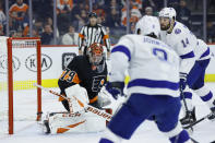Philadelphia Flyers' Carter Hart (79) blocks a shot as Tampa Bay Lightning's Tyler Johnson (9) and Pat Maroon (14) look on during the first period of an NHL hockey game, Saturday, Jan. 11, 2020, in Philadelphia. (AP Photo/Matt Slocum)