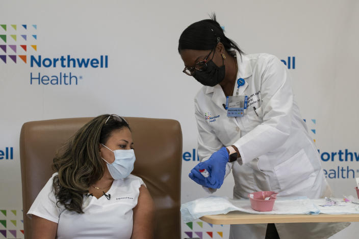 Michelle Chester, director of employee health services at Northwell Health, right, shows the Moderna COVID-19 vaccine to Arlene Ramirez, director of patient care at Long Island Jewish Valley Stream hospital, before administering the vaccine to her on Monday, Dec. 21, 2020, in Valley Stream, N.Y. (Eduardo Munoz/Pool via AP)