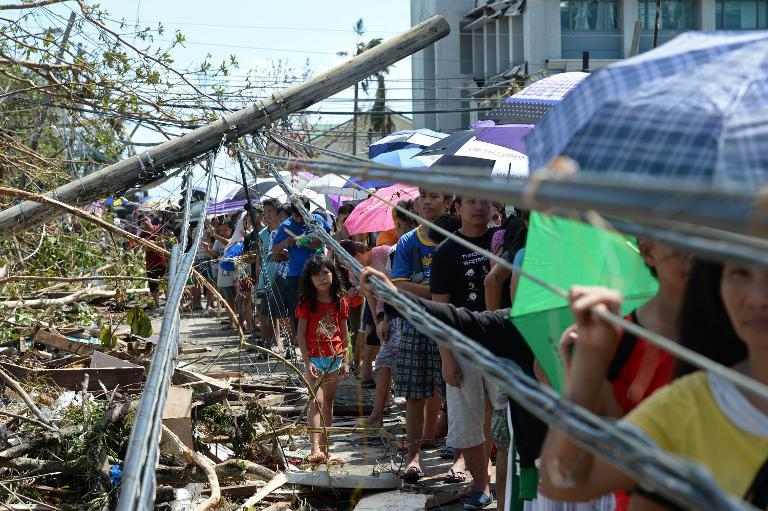 Residents queue up for relief food next to a fallen power line in Tacloban City, Leyte province, central Philippines on November 10, 2013, three days after devastating Typhoon Haiyan hit the city