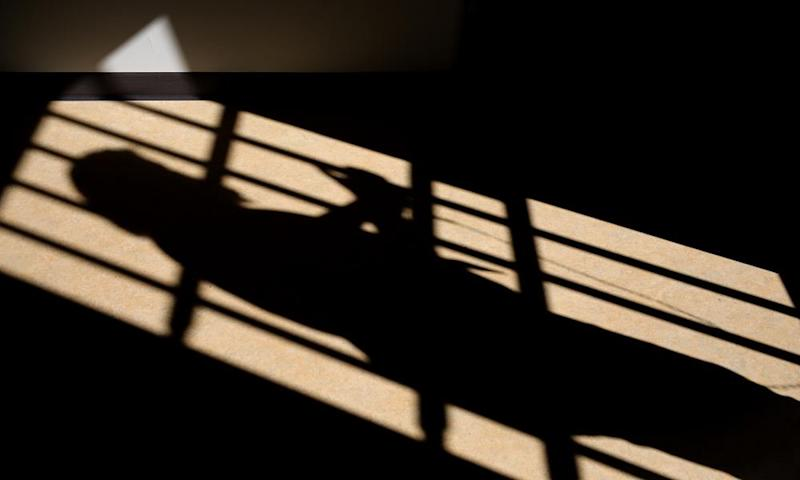 Silhouette of a man in a prison cell