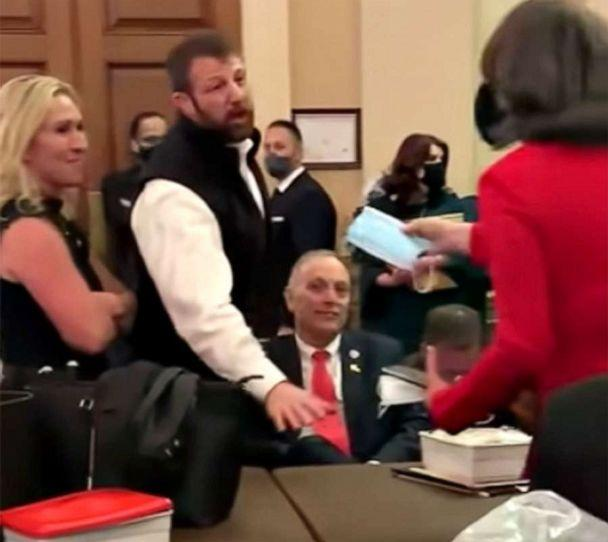 PHOTO: Rep. Markwayne Mullin turns down a mask in a crowded room while under lockdown in the Capitol during the riot by Trump supporters, as Rep. Marjorie Taylor Greene and Rep. Andy Biggs look on in Washington, D.C., Jan. 6, 2021. (via Punchbowl News )