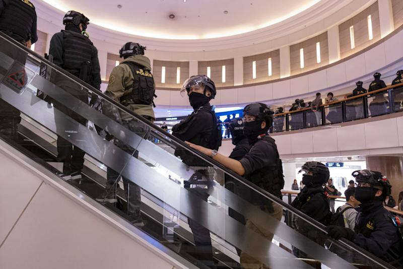 Riot police ride an escalator as they patrol the Harbour City shopping mall in the Tsim Sha Tsui district of Hong Kong, China, on Tuesday, Dec. 31, 2019. | Justin Chin—Bloomberg