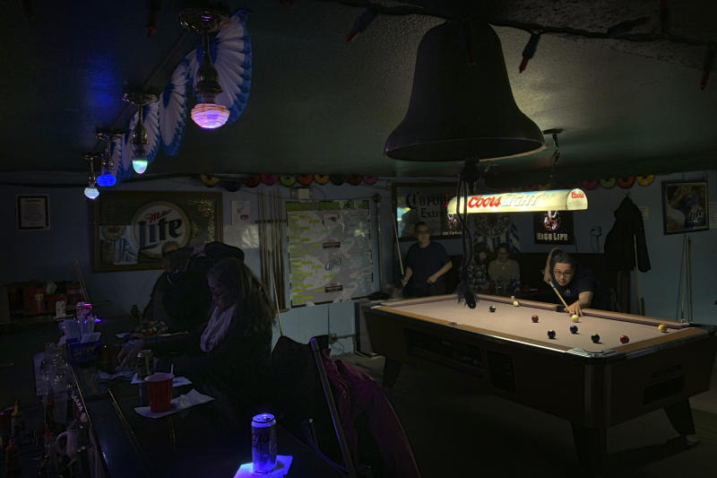 In this Feb. 23, 2019, photo, people play pool while some sit at the bar with their drinks at Soap and Suds, a popular nighttime spot on Front Street in Nome, Alaska. (AP Photo/Wong Maye-E)
