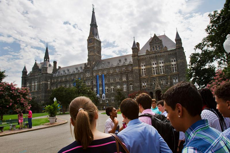 In this July 10, 2013, file photo, prospective students tour Georgetown University's campus in Washington. Federal authorities have charged college coaches and others in a sweeping admissions bribery case in federal court.