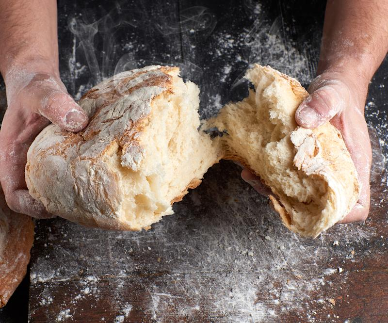 male hands breaking open baked bread in half over black wooden table