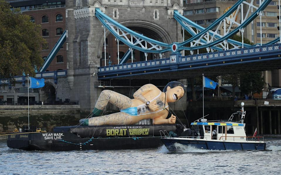 A giant inflatable in the shape Borat floats on a barge beneath Tower Bridge promoting the release of the new Sacha Baron Cohen film - PA