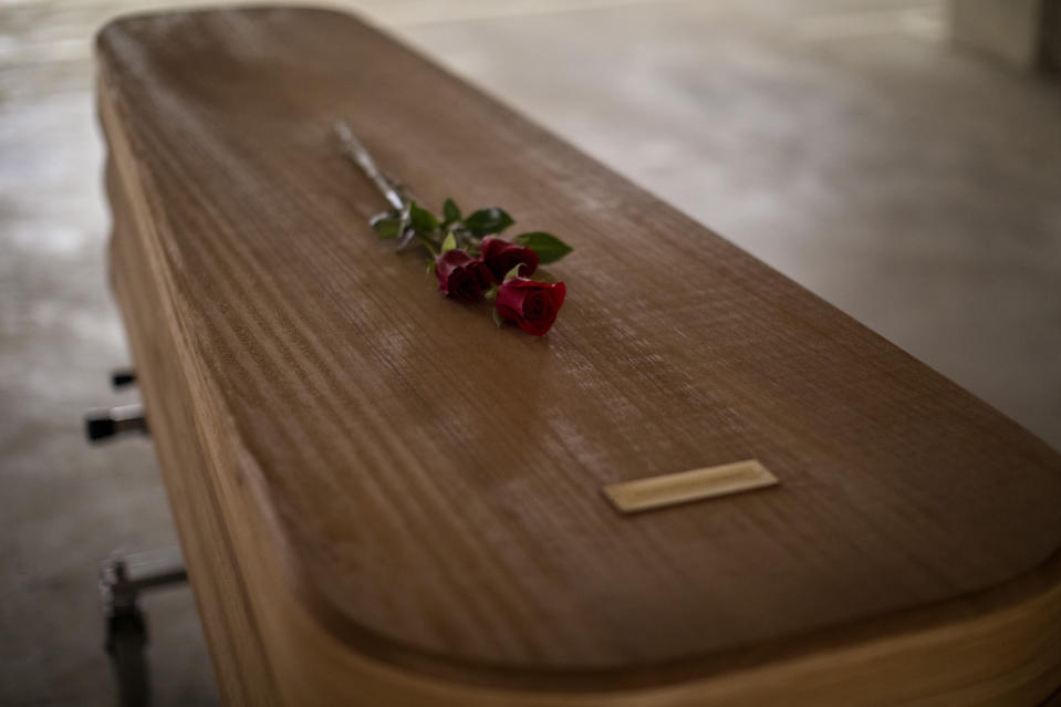 Flowers lie on the coffin of the last COVID-19 victim stored at an underground parking garage that was turned into a morgue, at the Collserola funeral home in Barcelona, Spain. May 17, 2020. A funeral home in Barcelona has closed a temporary morgue it had set up inside its parking garage to keep the victims of the Spanish city's coronavirus outbreak. The last coffin was removed and buried on Sunday. In 53 days of use, the temporary morgue has held more than 3,200 bodies. (AP Photo/Emilio Morenatti)