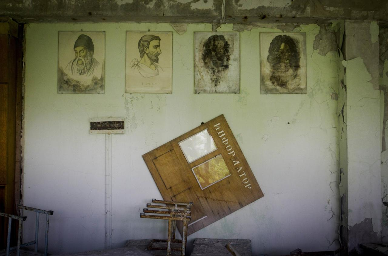 In this June 8, 2011 photo, portraits of ancient physicists and mathematicians hang on a wall in a school in the deserted town of Pripyat, Ukraine, some 3 kilometers (1.86 miles) from the Chernobyl nuclear plant. Chernobyl and Fukushima are some 5,000 miles apart but have much in common. The towns nearest to each of these stricken nuclear power stations, in Ukraine and Japan, whose disasters struck 25 years apart, already reveal eerie similarities. (AP Photo/Sergey Ponomarev) ONE OF PAIR NO. 6