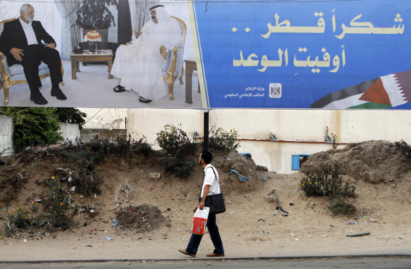 """Palestinian youth walks near a poster of Gaza's Hamas Prime Minister Ismail Haniyeh, left, and Emir of Qatar Sheikh Hamad bin Khalifa al-Thani in Gaza City, Sunday, Oct. 21, 2012. The poster announces the coming visit of the Emir of Qatar, it reads, """"Thank You Qatar."""" (AP Photo/Hatem Moussa)"""