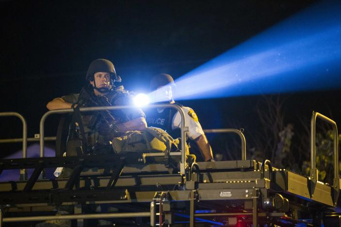 A police officer points a spotlight at a more vocal and confrontational group of demonstrators during further protests in reaction to the shooting of Michael Brown, near Ferguson, Missouri August 18, 2014. Police fired tear gas and stun grenades at protesters in Ferguson, Missouri on Monday, after days of unrest sparked by the fatal shooting of an unarmed black teenager by a white policeman. REUTERS/Lucas Jackson (UNITED STATES - Tags: CIVIL UNREST CRIME LAW TPX IMAGES OF THE DAY)