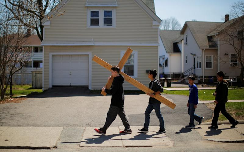 The faithful carry a cross between the Catholic Churches in Quincy to pray the Stations of the Cross on Good Friday Original description: Fifteen year-old Joe Desmond (L) and fourteen year-old Jose Las carry a cross between the Catholic Churches in Quincy, Massachusetts, U.S., to pray the Stations of the Cross on Good Friday April 14, 2017 - Credit: BRIAN SNYDER/REUTERS