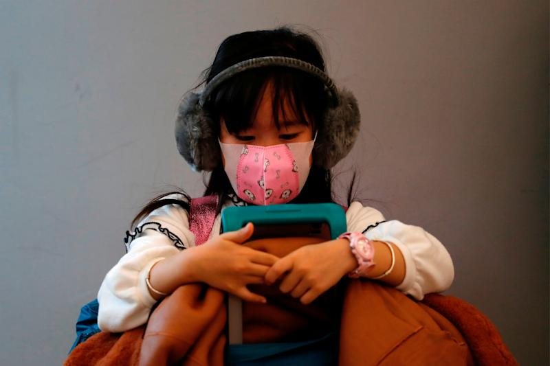 A child wears mask to prevent an outbreak of a new coronavirus at the Hong Kong West Kowloon High Speed Train Station, in Hong Kong, China January 23, 2020. REUTERS/Tyrone Siu TPX IMAGES OF THE DAY