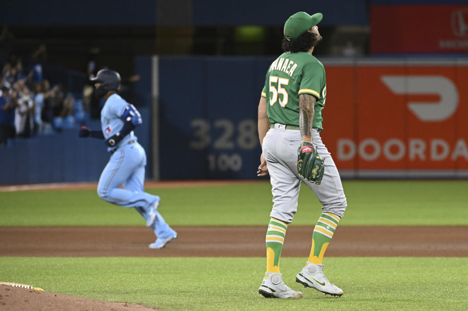 Toronto Blue Jays' Teoscar Hernandez, left, rounds the bases after hitting a two-run home run off Oakland Athletics' starting pitcher Sean Manaea (55) during the fourth inning of a baseball game Friday, Sept. 3, 2021, in Toronto. (Jon Blacker/The Canadian Press via AP