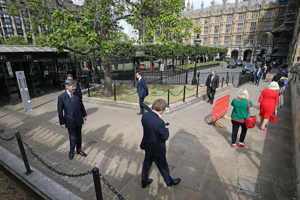 Members of Parliament, including Leader of the House of Commons Jacob Rees-Mogg, queue outside the House of Commons in Westminster, London, as they wait to vote on the future of proceedings, amid a row over how Commons business can take place safely. (Photo by Jonathan Brady/PA Images via Getty Images)