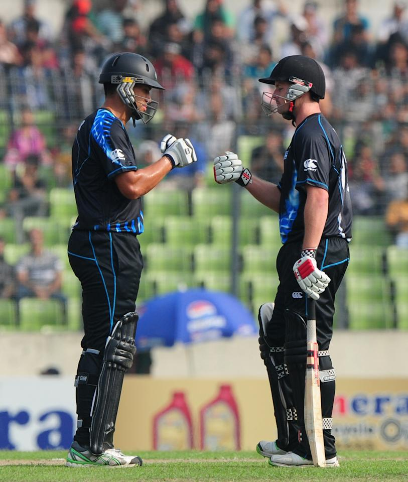 New Zealand batsman Colin Munro (R) celebrates with teammate Ross Taylor after scoring a boundary during the T20 match between Bangladesh and Zew Zealand at the Sher-e-Bangla National Cricket Stadium in Dhaka on November 6, 2013. AFP PHOTO/ Munir uz ZAMAN        (Photo credit should read MUNIR UZ ZAMAN/AFP/Getty Images)