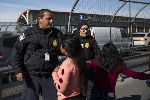 """Customs and Border Patrol agents stop a woman and her daughter at the International Boundary Line of the Paso del Norte Port of Entry between Juarez and El Paso on Nov. 28, 2018. The mother did not verbally declare asylum to the agents before a private security officer explained they sign up to be put on """"the list"""" for entry to ask for asylum. (Photo: Adria Malcolm for Yahoo News)"""