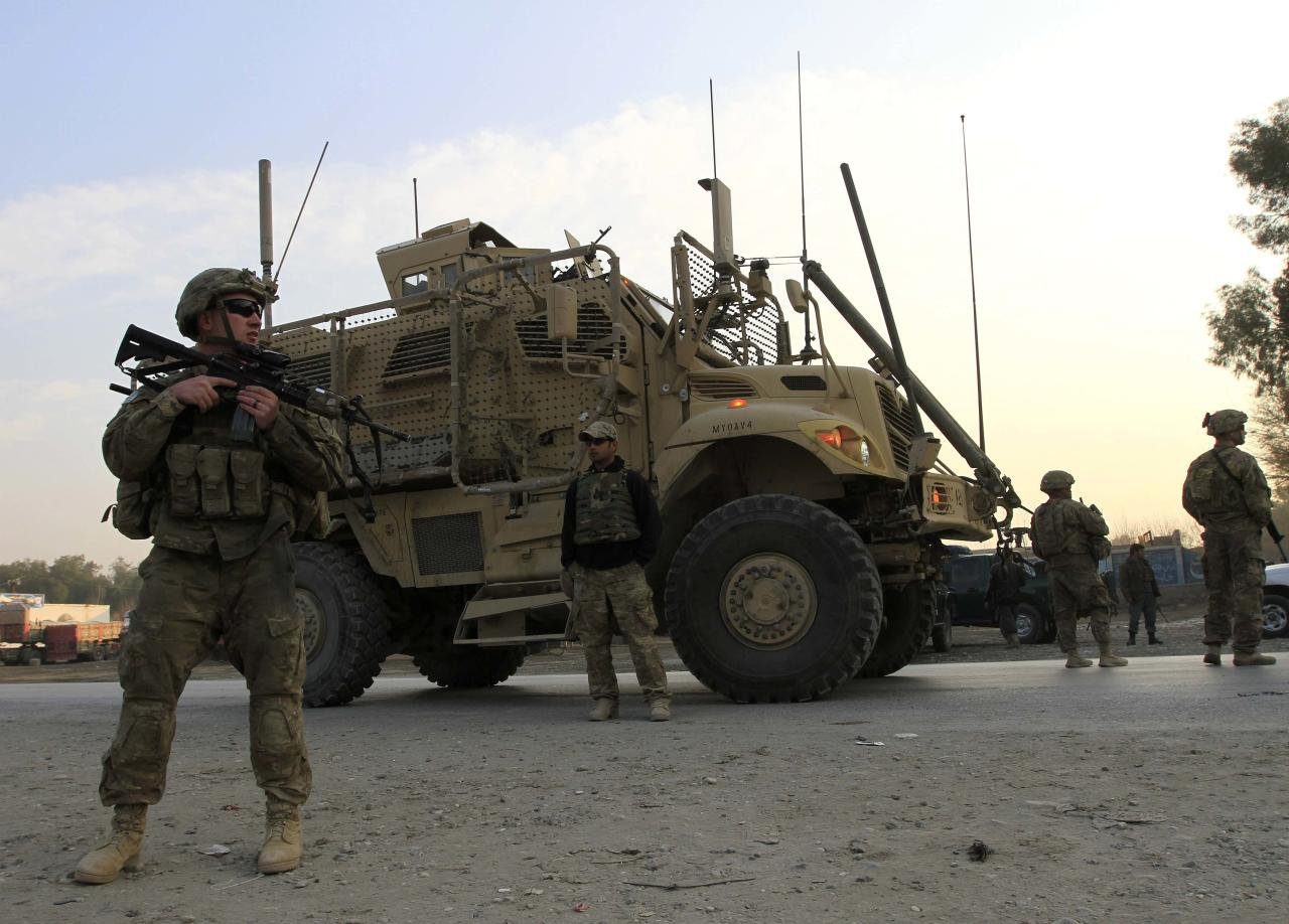 U.S. troops keep watch at the site of a suicide attack on the outskirts of Jalalabad, January 5, 2015. A suicide attacker targeted a U.S. convoy on the outskirts of Jalalabad on Monday but so far no causalities have been reported yet, provincial spokesman Ahmadzia Abdulzai said.  REUTERS/ Parwiz (AFGHANISTAN - Tags: CIVIL UNREST POLITICS MILITARY)