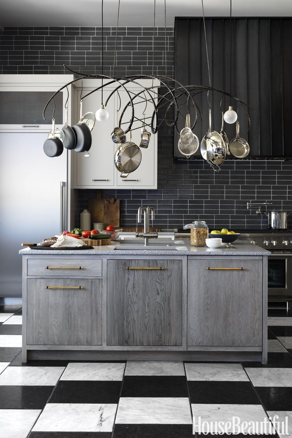 "<p>A glazed backsplash and weathered oak island feel sleek and sexy in this <span class=""redactor-unlink"">kitchen by Jon de la Cruz</span>. Plus, the hanging rack is functional <em>and</em> stylish. If you love the monochrome look but want a little more soul, take note. </p>"
