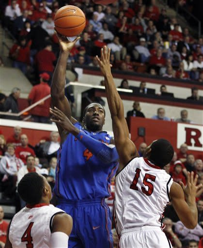 Florida's Patric Young (4) shoots over Rutgers' Derrick Randall and Myles Mack (4) during the first half of an NCAA college basketball game in Piscataway, N.J., Thursday, Dec. 29, 2011. (AP Photo/Mel Evans)