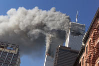 <p>Smoke rises from the burning twin towers of the World Trade Center after hijacked planes crashed into the towers. (Reuters)</p>