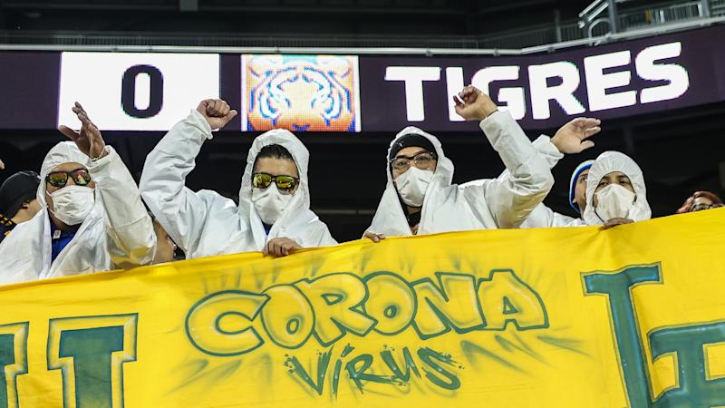 UANL Tigres fans hold a sign while wear hazmat suits and a medical masks during the first half against NYCFC at Red Bull Arena. (Vincent Carchietta-USA TODAY Sports)