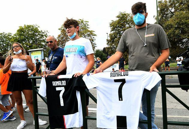 Two supporters pose with T-shirt of Juventus' Portuguese forward Cristiano Ronaldo, outside the Juventus' Continassa training centre in Turin on August 27,2021. - Cristiano Ronaldo will not train with Juventus on August 27, the Serie A giants confirmed to AFP, as rumours of an imminent move to Manchester City gather pace. Widespread media reports said that Ronaldo left Juve's Continassa training centre before the start of the August 27 session. Sky Sport Italia reported that the five-time Ballon d'Or winner arrived in the morning to say goodbye to his teammates before leaving at around 10:45 am local time (0845 GMT). Asked by AFP if Ronaldo would be training with his Juve teammates, a club spokeswoman confirmed that he would not. (Photo by - / AFP) (Photo by -/AFP via Getty Images) (Photo: - via Getty Images)