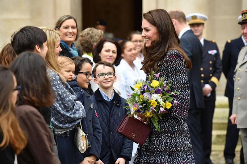 The Duchess of Cambridge receives flowers as she arrives at the Bataclan: PA