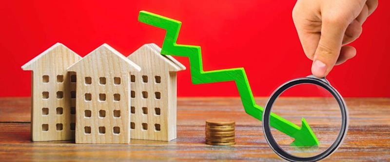 Miniature wooden houses and a green arrow down. The concept of falling mortgage rates
