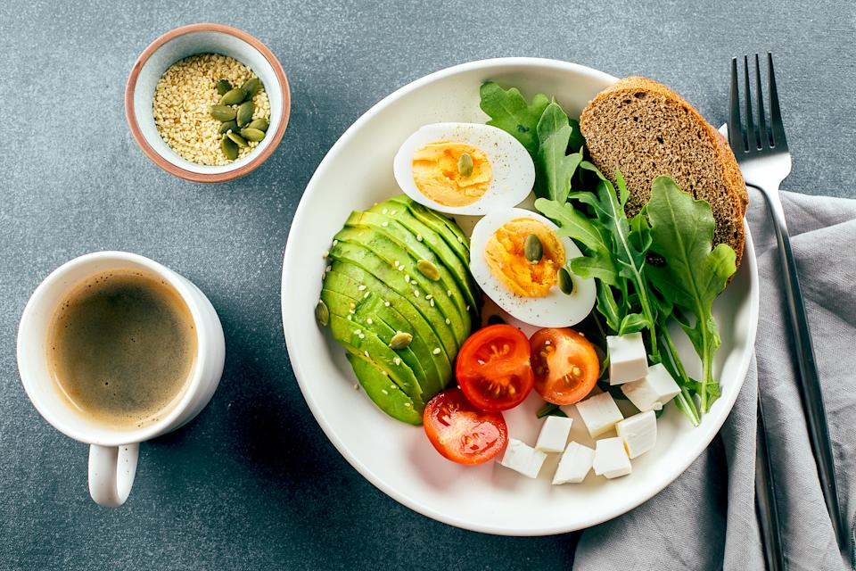 Healhty vegan breakfast bowl. Avocado, egg, tomato, feta cheese, arugula and bread and cup of coffee. Top view
