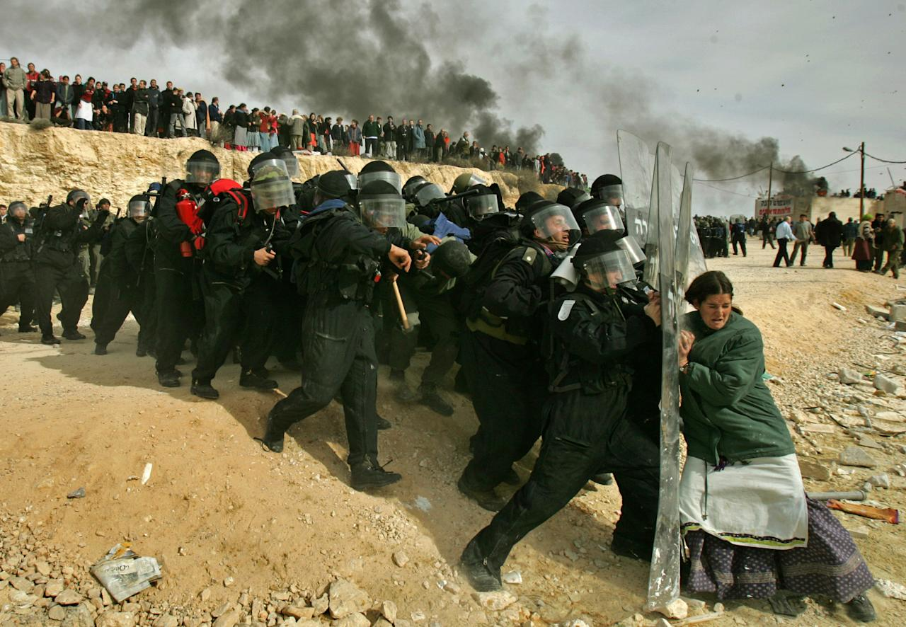 <p>A Jewish settler struggles with an Israeli security officer during clashes that erupted as authorities evacuated the West Bank settlement outpost of Amona, east of the Palestinian town of Ramallah, on Feb. 1, 2006. Oded Balilty of the Associated Press won the Pulitzer Prize for breaking news photography for this image. (Photo: Oded Balilty/AP) </p>