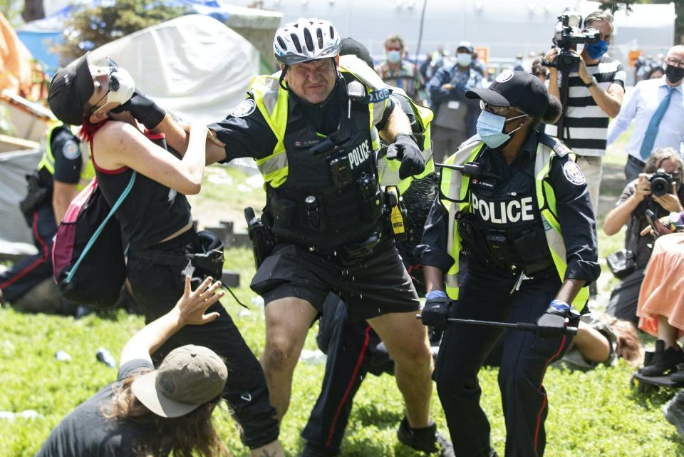 """<span class=""""caption"""">Police remove encampment supporters as they clear Lamport Stadium Park encampment in Toronto on July 21, 2021.</span> <span class=""""attribution""""><span class=""""source"""">THE CANADIAN PRESS/Chris Young </span></span>"""