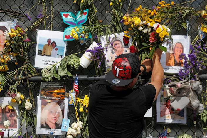 A man places flowers on a makeshift memorial for the victims of the Surfside's Champlain Towers South condominium collapse in Miami, Florida (Shannon Stapleton / Reuters)