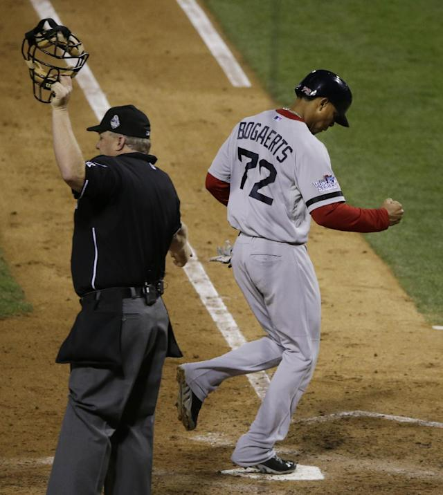 Boston Red Sox shortstop Xander Bogaerts punches the air as he scores on an RBI ground rule double by David Ross during the seventh inning of Game 5 of baseball's World Series Monday, Oct. 28, 2013, in St. Louis. (AP Photo/Charlie Neibergall)