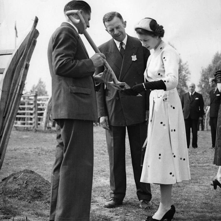 Queen Elizabeth reading the inscription on the spade with which she planted the Queen's Tree to commemorate her coronation - PA Archive