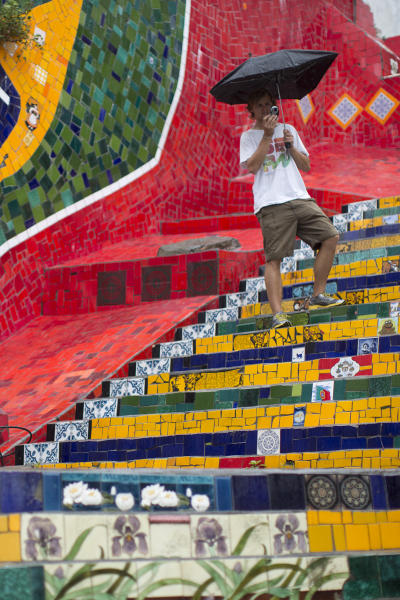 """Tourist from Germany take photos on a stairway that was decorated by Chilean artist Jorge Selaron, which he titled the """"Selaron Stairway"""" in Rio de Janeiro, Brazil, Thursday, Jan. 10, 2013. Selaron, an eccentric Chilean artist and longtime Rio resident who created a massive, colorful tile stairway in the bohemian Lapa district that's popular with tourists, was found dead on the stairway on Thursday. He was 54. Authorities are investigating the cause of death. (AP Photo/Felipe Dana)"""