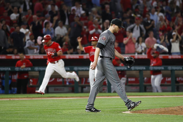 Arizona Diamondbacks starting pitcher Matt Koch walks back to the mound as Los Angeles Angels' Kole Calhoun, background left, runs the bases after hitting a home run during the sixth inning of a baseball game Tuesday, June 19, 2018, in Anaheim, Calif. (AP Photo/Jae C. Hong)