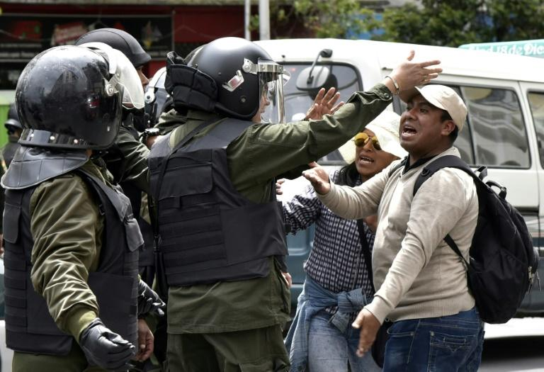 People argue with policemen during a march against the nomination of Bolivian President Evo Morales as a candidate for reelection for the October 2019 elections, during a national strike, in La Paz, on December 6, 2018