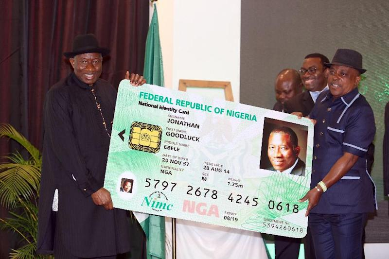 Nigerian President Goodluck Jonathan (L) holds a replica of his electronic ID card with chairman of the board of National Identity Management Commission Uche Secoundus during the cards' launch in Abuja, August 28, 2014 (AFP Photo/Philip Ojisua)