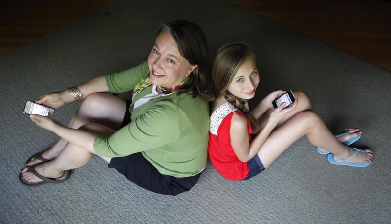 In this Thursday, May 24, 2012 photo, Anna Schiferl, right, sits with her mother, Joanna, holding their cell phones in the living room of their LaGrange, Ill., home. Statistics from the Pew Internet & American Life Project show that, these days, many people with cell phones prefer texting over a phone call. It's not always young people, though the data indicates that the younger you are, the more likely you are to prefer texting. But many experts say the most successful communicators will, of course, have the ability to do both talk or text, and know the most appropriate times to use those skills. (AP Photo/Charles Rex Arbogast)