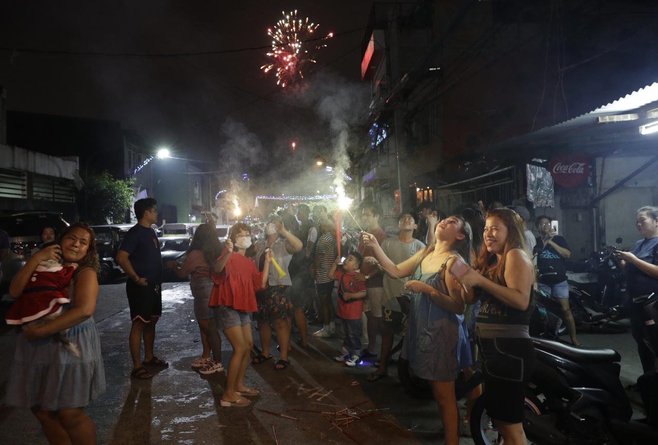 Filipinos light fireworks along a street as they celebrate the coming of the New Year early Wednesday, Jan. 1, 2020 in Manila, Philippines. Filipinos welcome the New Year with noise and firecrackers in the belief that this will drive away bad spirits and bring in good luck. (AP Photo/Aaron Favila)