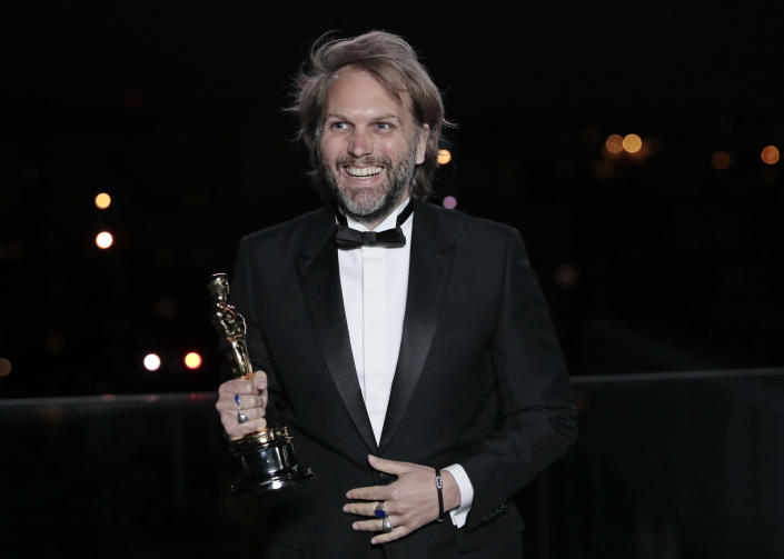 Florian Zeller smiles as he holds his Oscars statuette after winning the Best Adapted Screenplay for the 'The Father' at a screening of the Oscars on Monday April 26, 2021 in Paris, France. (AP Photo/Lewis Joly, Pool)