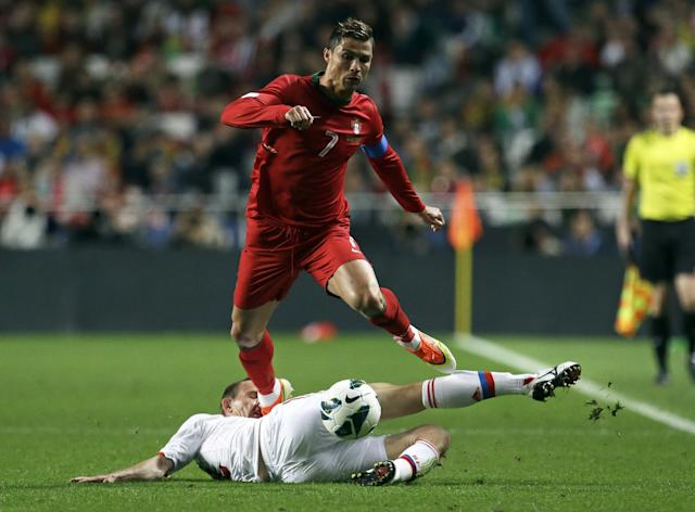 FILE - In this June 7, 2013, file photo, Portugal's Cristiano Ronaldo gets the ball past Russia's Alexei Kozlov, on the ground, during their 2014 World Cup qualifying group F soccer match, at the Luz stadium in Lisbon. (AP Photo/Armando Franca, File)