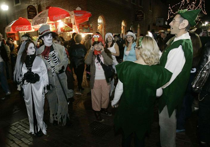 A couple dressed as elves pass a couple dressed as ghouls on Halloween in Salem, Mass., in 2007.