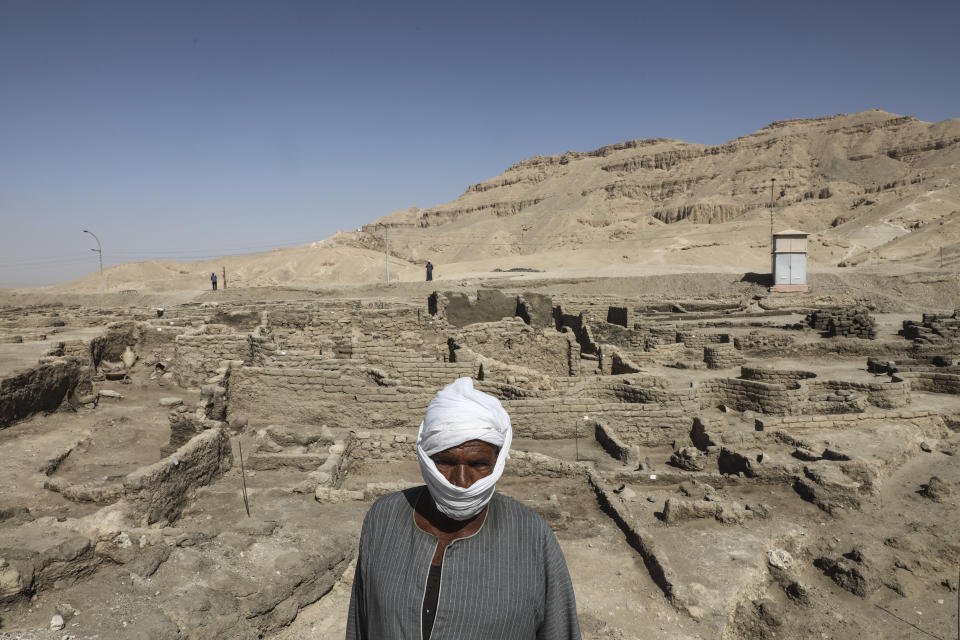 Worker stands in a 3,000-year-old lost city in Luxor province, Egypt, Saturday, April 10, 2021. The newly unearthed city is located between the temple of King Rameses III and the colossi of Amenhotep III on the west bank of the Nile in Luxor. The city continued to be used by Amenhotep III's grandson Tutankhamun, and then his successor King Ay. (AP Photo/Mohamed Elshahed)